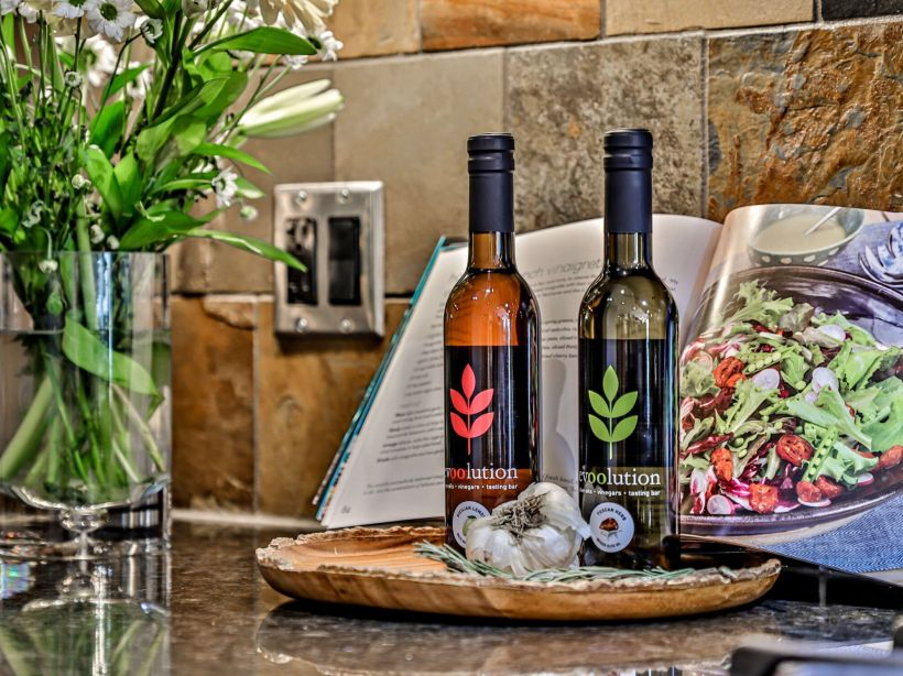 a granite countertop in a vacation rental at Spring Creek Vacations with two bottles of olive oil atop it and a cook book propped up behind them.