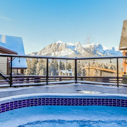 Mountain view of Canmore from the perspective of the hot tub at Spring Creek Vacations, during a bright blue skied day.