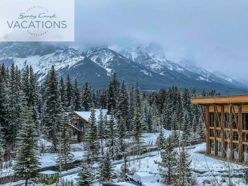 A building stands on the right, while snowcovered trees stand on the left, with mountains in the background and a low snow fog above in Canmore, Alberta at Spring Creek Vacations