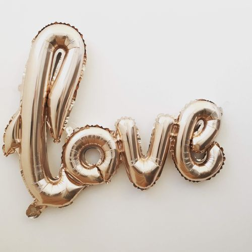 The word 'love' in a rose-gold balloon