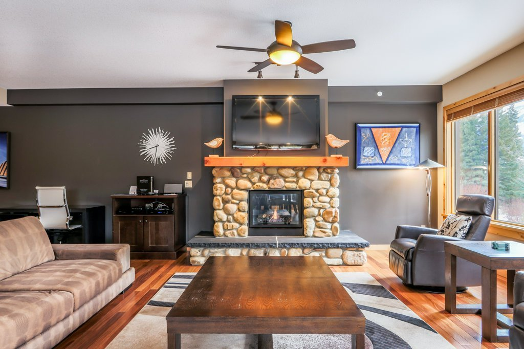living room with fireplace and tv in #110 Rundle Cliffs Lodge