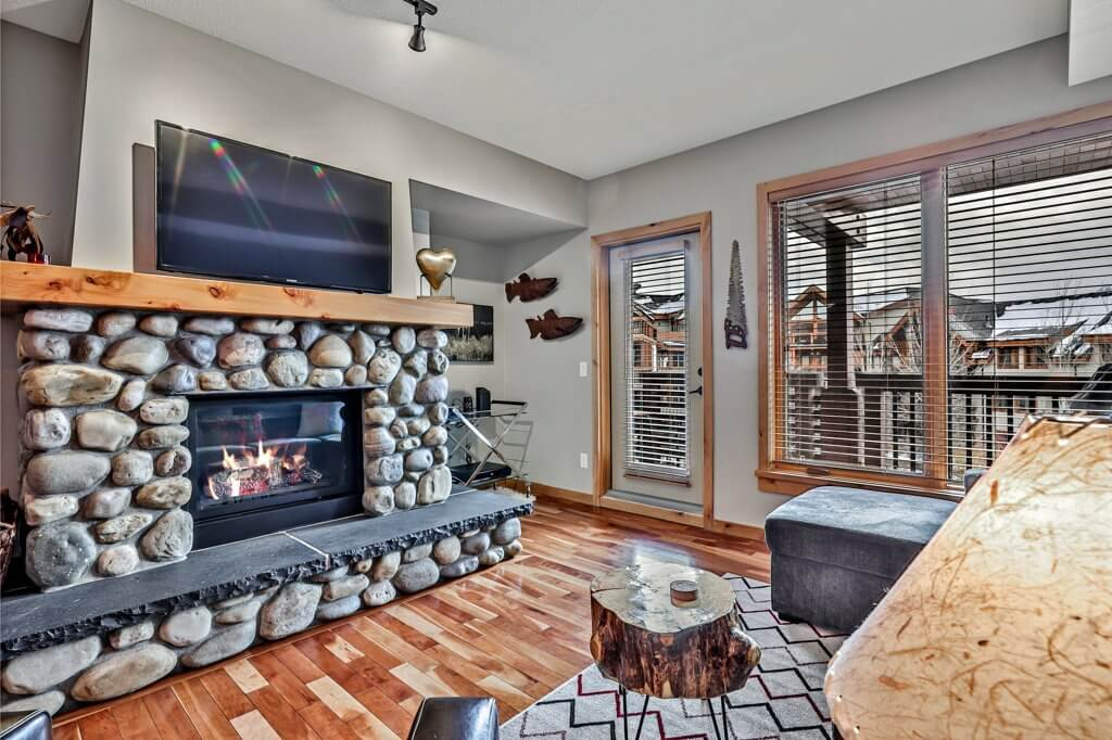 Living room at Spring Creek Vacations suite with a stone fireplace  and deck.