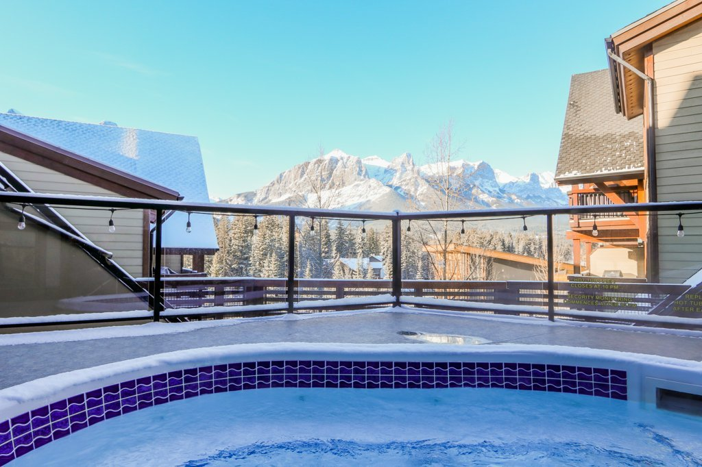 hot tub with view of the mountains in Rundle Cliffs Lodge