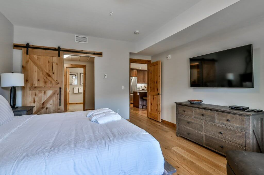 A comfortable, large bed with white linen in a bedroom with a large wall TV, wooden storage and wooden floors, in a luxury Spring Creek Vacations suite, in Canmore, Alberta.