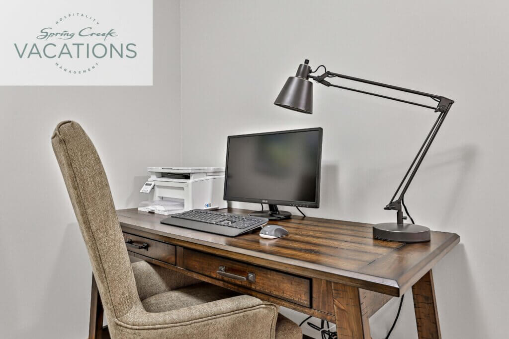 The workstation is in the corner of a room. There is a wooden table on the corner. The table has a printer, a monitor with its mouse and keyboard and a lamp. In front of the table, there is a chair made of fabric.