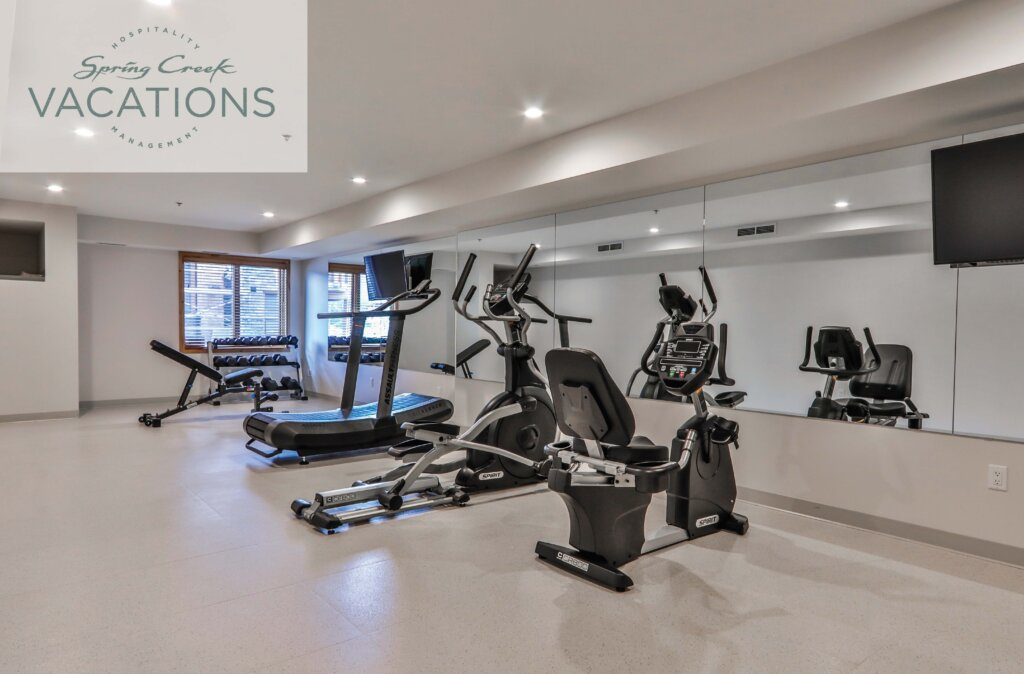 Brightly lit gym with exercise equipment and machines at Spring Creek