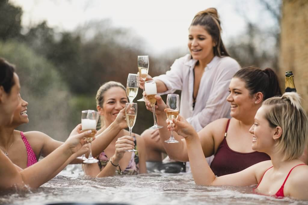 Five girls in a hot tub holding up wine glasses to cheers each other at Spring Creek Vacations