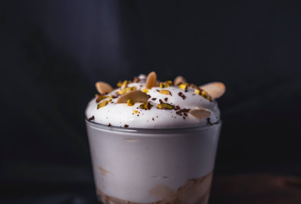 coffee in a clear glass cup, with whipped topping and a sprinkle of pistachios