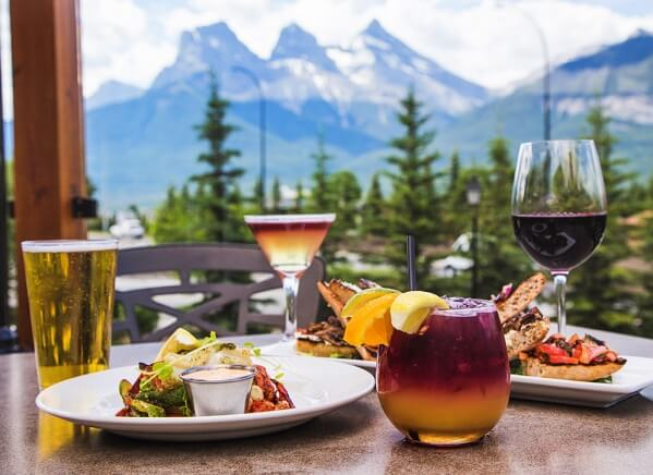 two plates of foot, and a glass of beer and a cocktail on a table overlooking the Three Sisters Mountains in Canmore, Alberta