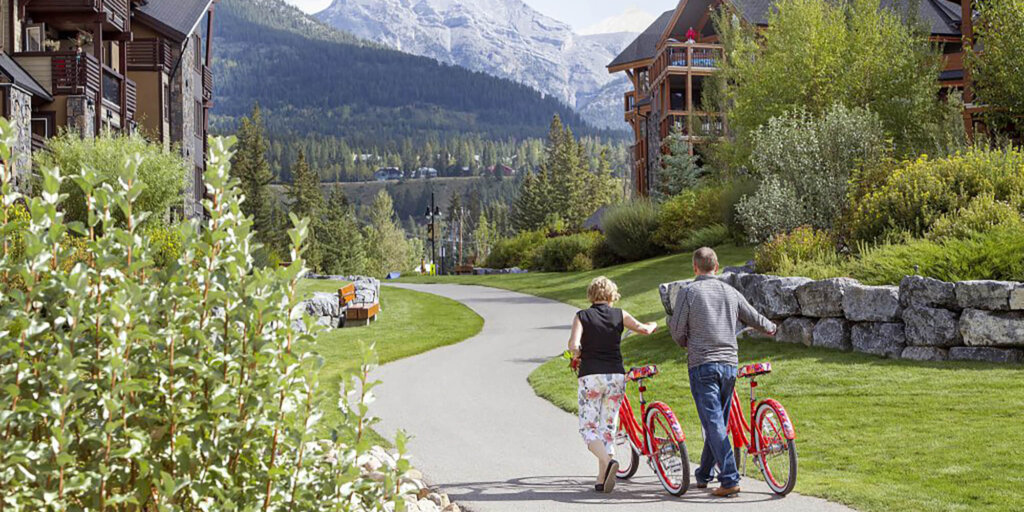 A couple with red bicycles walk along a winding path through green foliage, with stunning views of Canmore mountains in the background