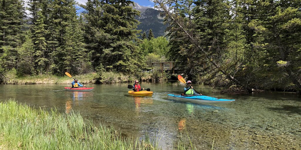 Three kayakers in a creek in Canmore, Alberta.