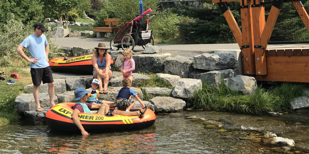 Three children and three adults at the edge of a creek in Spring Creek Mountain Village, with one adult and two children in an Explorer 200 floatation device.