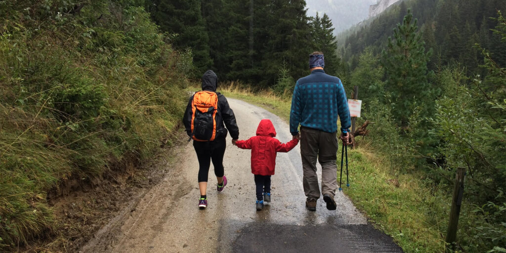 Two adults walk along rainy road with small child between them, holding hands