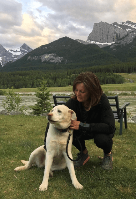 Katherine, part-time front desk at Spring Creek Vacations, with her yellow lab in a park in Canmore