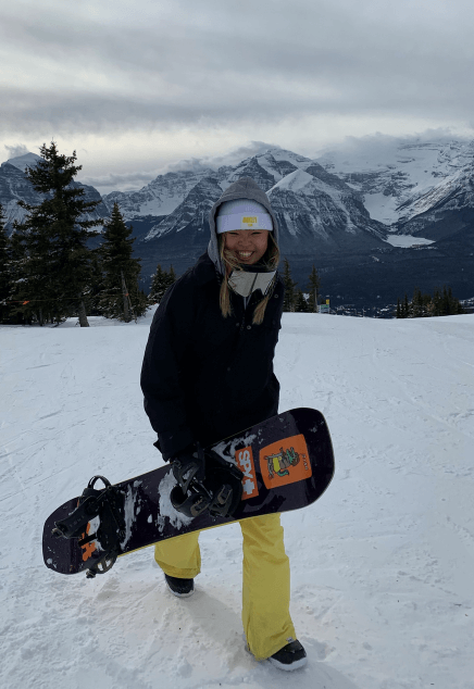 Wakana, full-time front desk at Spring Creek Vacations, with her snowboard on a mountain near Canmore