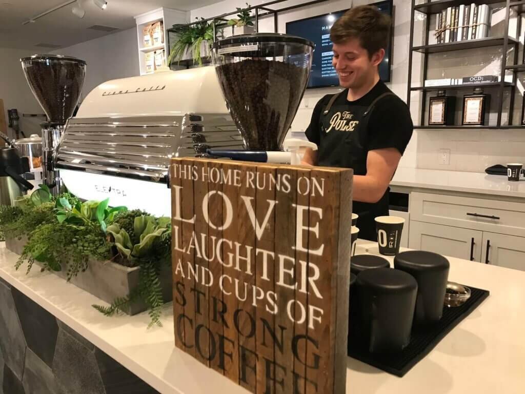 Male barista at The Pulse Coffee Shop and General Store in Spring Creek stands behind an espresso machine, smiling.